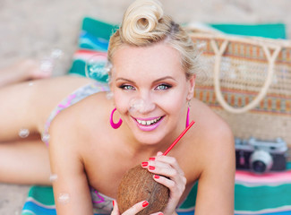 cheerful beautiful young woman lying on the beach with vintage c