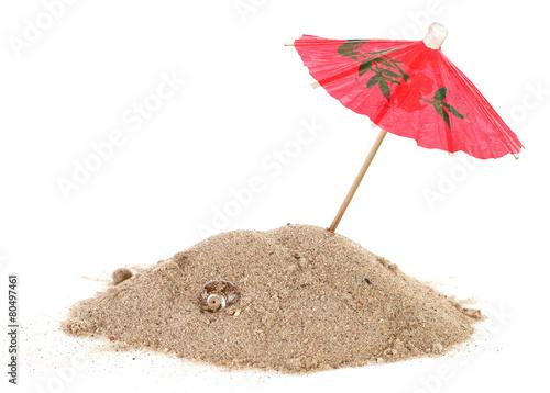 Leinwandbild Motiv Cocktail Umbrella in Sand Mound with Shells