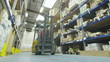 Forklift truck driver in a factory or warehouse driving between rows of shelving