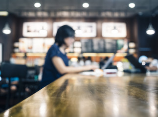 Woman working with laptop on table in blurred cafe background