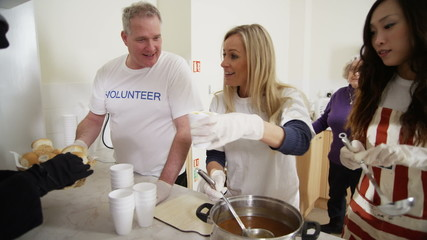 Soup kitchen volunteers help to feed the homeless