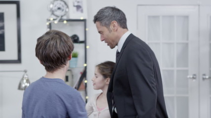 Businessman returns home from work and is greeted by his family