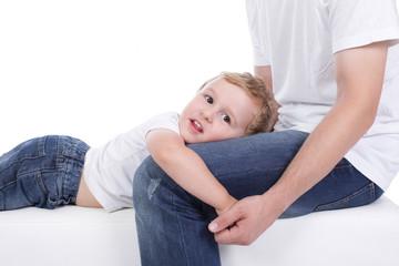 Entspanntes Kind liegt auf dem Schoß des Vaters
