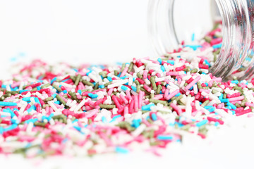 Spilled sprinkles with container on white background