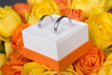 bouquet of orange and yellow rose flowers and wedding rings in b