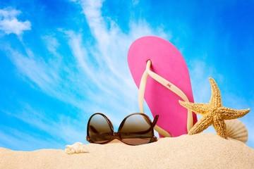 Beach. Flip-flops and sunglasses on sand beach.