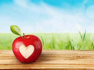 Heart Shape. Fresh red apple with heart symbol and leaf