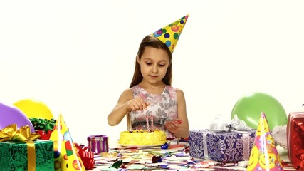 Beautiful girl decorates a cake with candles. On the table are