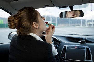 businesswoman looking in mirror at car and applying cosmetics