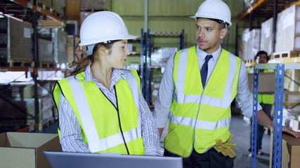 2 warehouse employees discuss stock and storage requirements