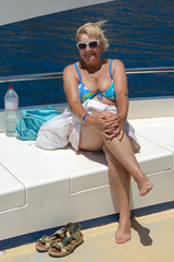 Senior woman on the yacht deck on sea water background.