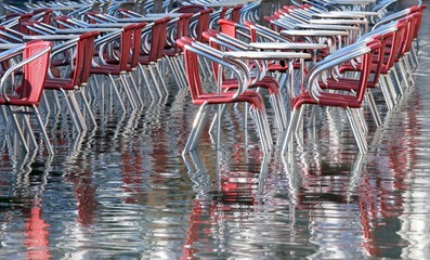 reflection on the water table and chairs in Venice during the fl