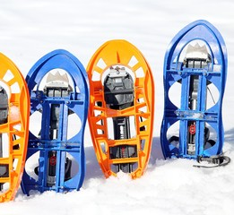 two pari of orange modern snowshoes in the mountain