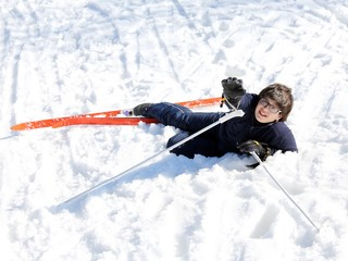 young boy asks for help after the fall on skis