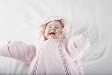 laughing baby face in pink snowsuit