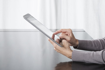 tablet in woman hands grey colors