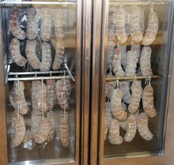sausages and cured meats in large fridge during the seasoning