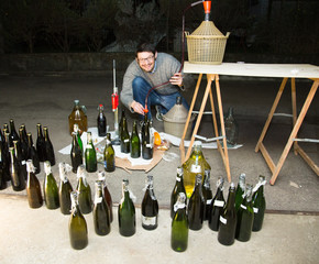 man bottling red wine from the demijohn to glass bottles