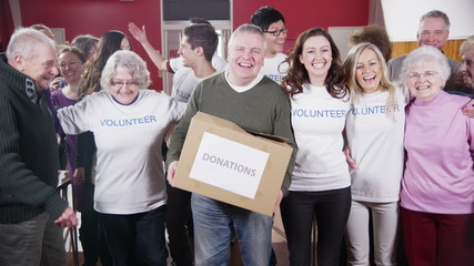 Large group of charity volunteers embrace and give big smiles into camera