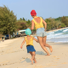 Little daughter running with mother on the beach