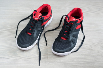 Running shoes with red trim flat on  floor
