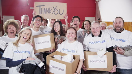 "Happy group of fundraisers holding donated goods and a ""Thank You"" sign"