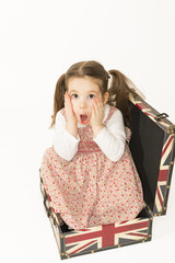 Little girl standing in suitcase beeing surprised