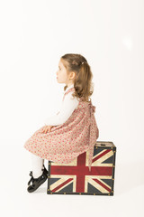 Little girl sitting on a old suitcase and waiting