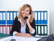 Frau mit blonden Locken im Büro lacht am Telefon