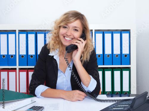 Frau mit blonden Locken im Büro lacht am Telefon - 80507046