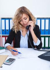 Frau mit blonden Locken im Büro am Telefon macht Notizen
