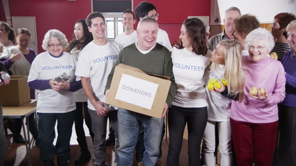 Large group of charity volunteers assemble and give big smiles into camera