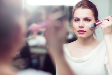 The girl with bright pink a make-up applies blush