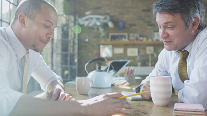 Two businessmen chatting over a cup of coffee