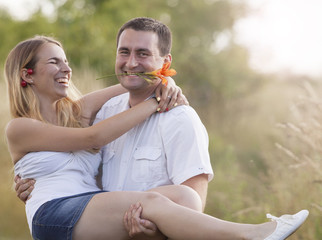 Happy couple. He is carying her in his arms, flower in mouth