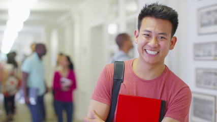 Portrait of a young male asian student standing in a busy college hallway