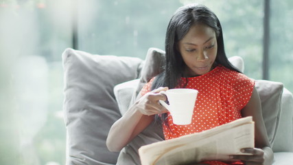 Attractive young woman relaxing at home with newspaper and cup of coffee