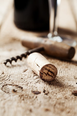 Wine cork and corkscrew, wine bottle and glass on the background