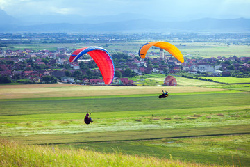 Paragliders flying over green fields