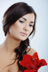 Pretty girl with red flower in her hand
