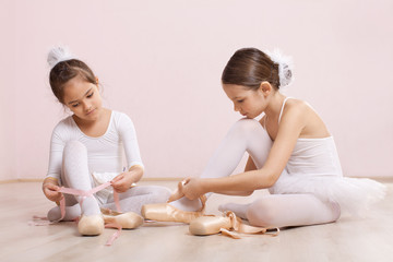 Two little ballerinas adjusting their slippers