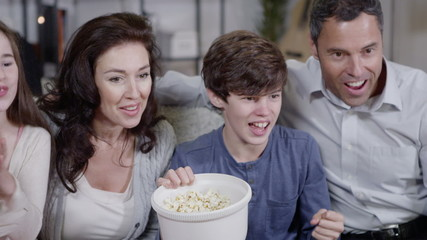Happy family watching sports on t.v. and spilling popcorn everywhere