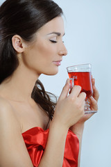 Beautiful woman in red breathes hot herbal tea