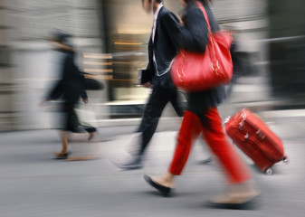 People with a red bag and a suitcase walking down the street