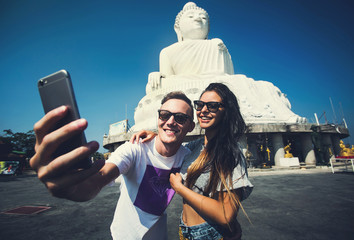Multiracial couple of students make selfie traveling in Asia