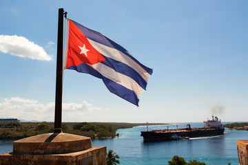Cuba flag waving on the wind with a big boat in background