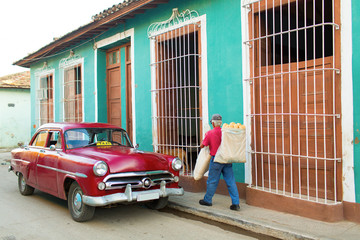 Streets of Trinidad, Cuba. Man delivering bread and old classic
