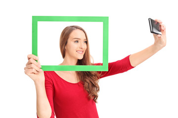 Beautiful girl taking a selfie behind picture frame
