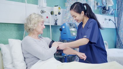 Attractive young nurse taking care of an elderly female patient