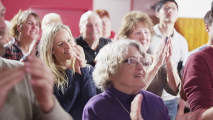 Mature male speaker addresses public meeting or church group